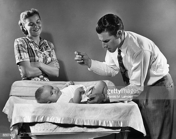 A cheerful mother and placid baby look on as a determined father attempts to fasten the baby's diapers with safety pins