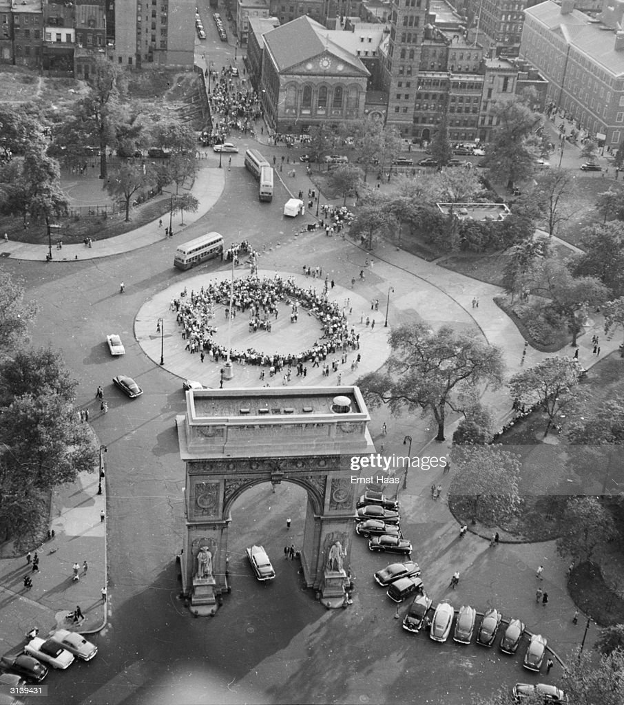 A crowd fills the roundabout in front of Washington Arch in Washington Square Park Greenwich Village New York