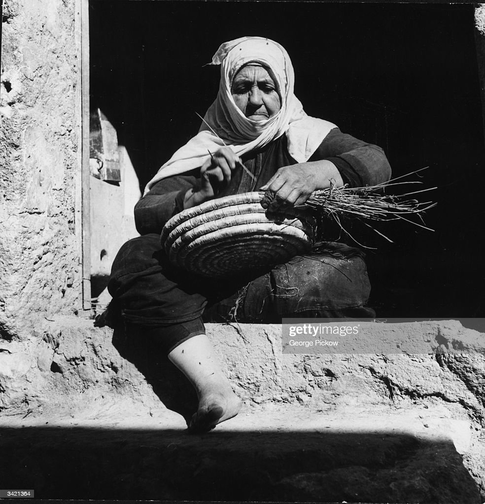 A Druze woman weaves a straw basket The Druze are a secretive Christian Arab sect