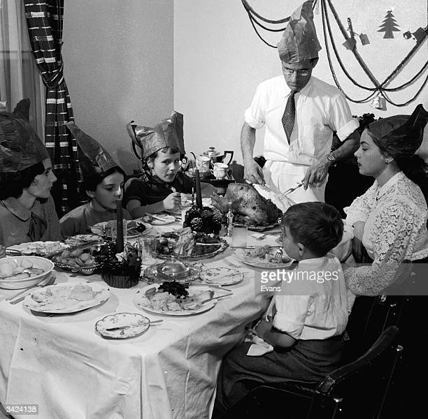 A family wearing festive paper hats watch while Dad carves the turkey for Christmas dinner