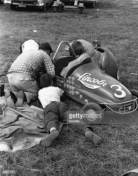 A father helping his sons work on their 2cylinder racing car