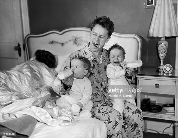 A father sits on the edge of his bed yawning as he feeds twin babies bottles of milk One of the babies cries as the mother sleeps behind them The man...