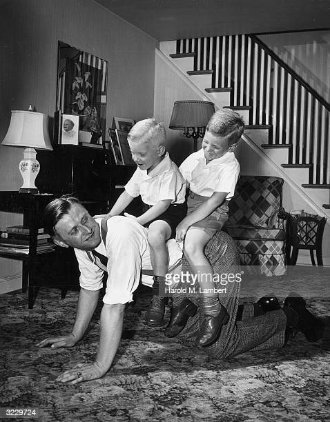 A father smiles as he crawls on his hands and knees on the living room floor giving his two sons a horseback ride 1950s The father wears suspenders...