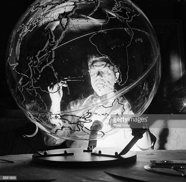 A geographer employed by the Farquhar company in Philadelphia at work on a threefoot diameter transparent globe He is surveying the area off the...