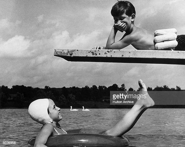A girl lays on a rubber tube raft smiling up at a boy who lays on a diving board She wears a swim cap He wears a life preserver belt Two swans float...