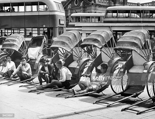 A group of rickshaw pullers take a rest whilst waiting for customers on the Kowloon peninsula where they can expect passengers from the ferry bus and...