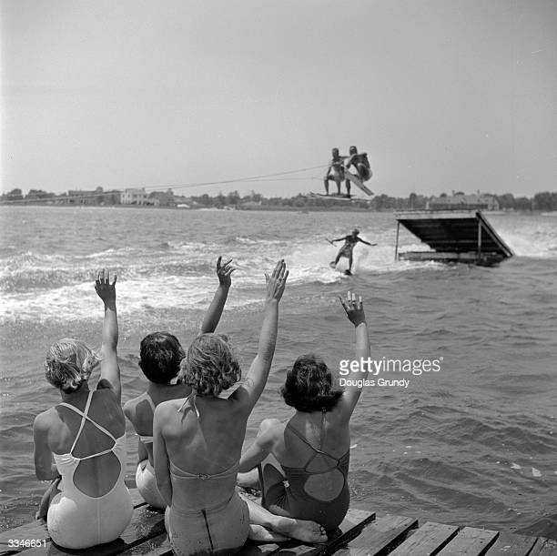 A group of women wave to their waterskiing friend as two skiers leap over her after jumping a ramp