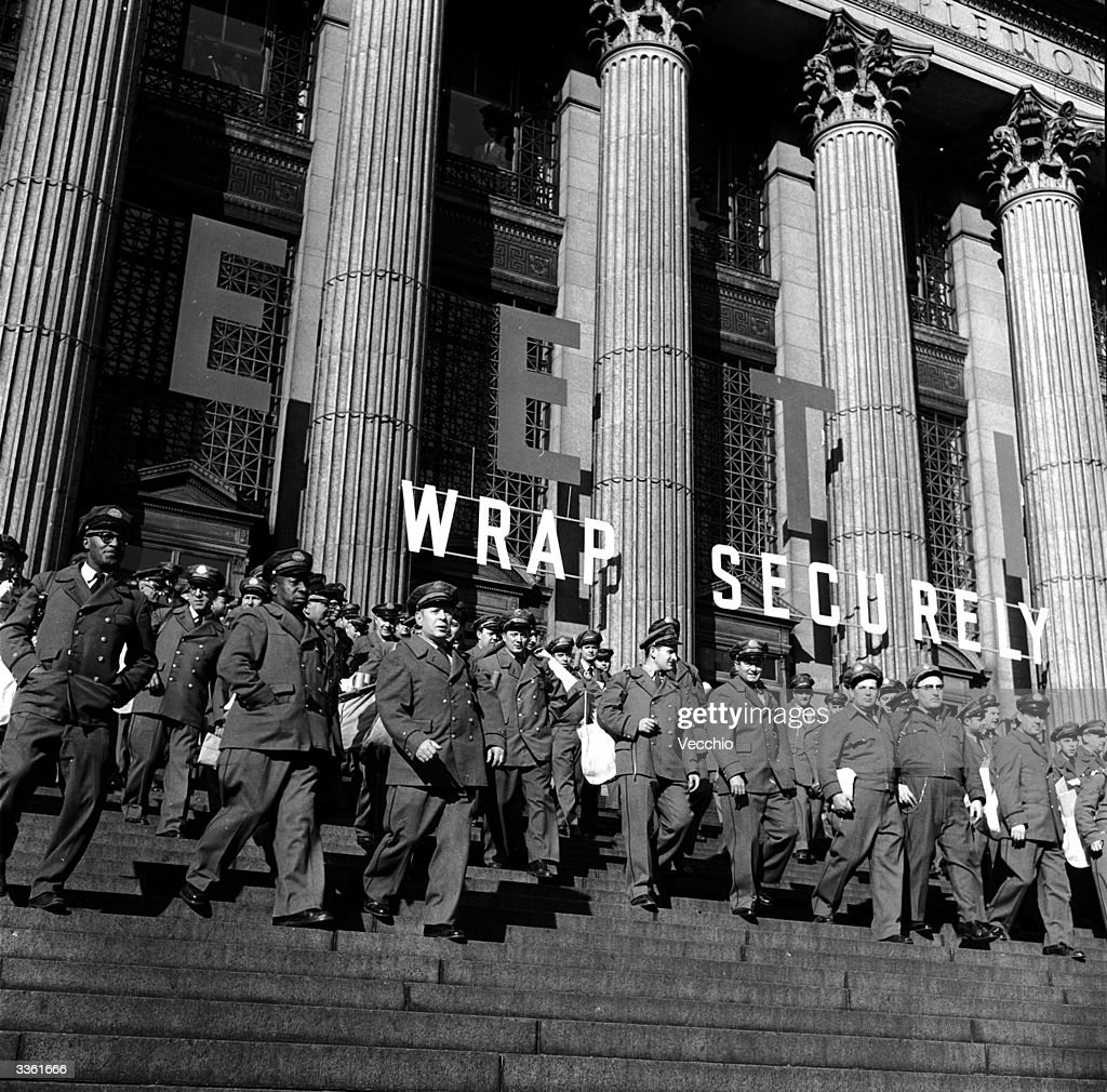 A large group of mailmen leaving the General Post Office early in the morning to start their rounds in New York City at Christmas.