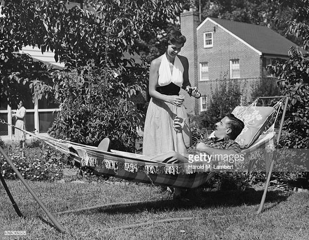 A man lays outdoors in a hammock in his backyard as his wife pours him a glass of beer from a bottle