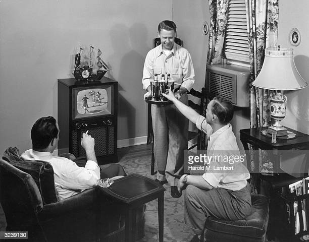 A man serves beer on a platter to his two friends as they all watch a baseball game in his living room