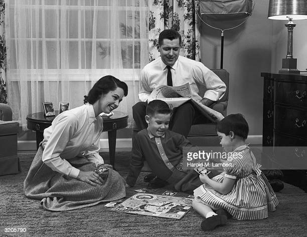 A man sits with his newspaper and watches his wife and two children playing a board game in their living room