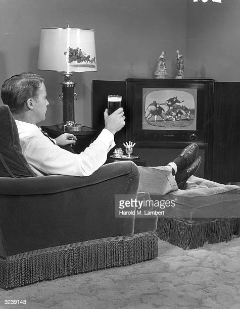 A man wearing slippers sits with his feet up drinking beer and smoking while watching a football game on television in his living room
