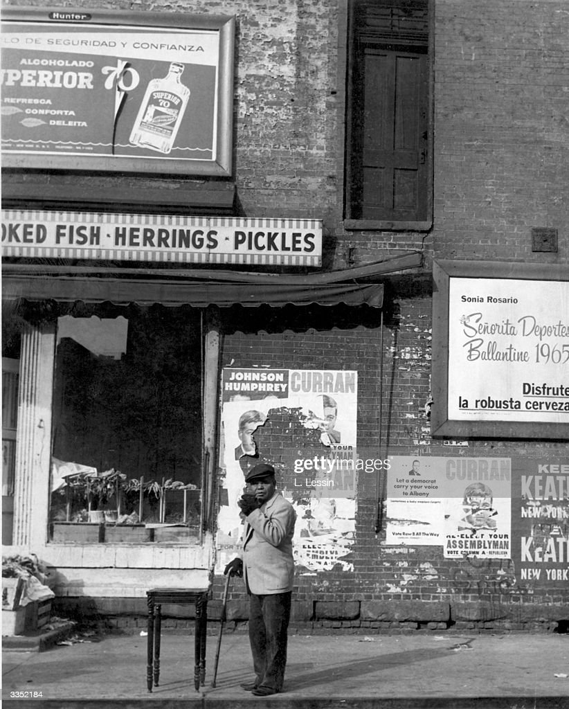 A Negro man with a walking stick and gloves stands beside an occasional table in the streets of Harlem New York