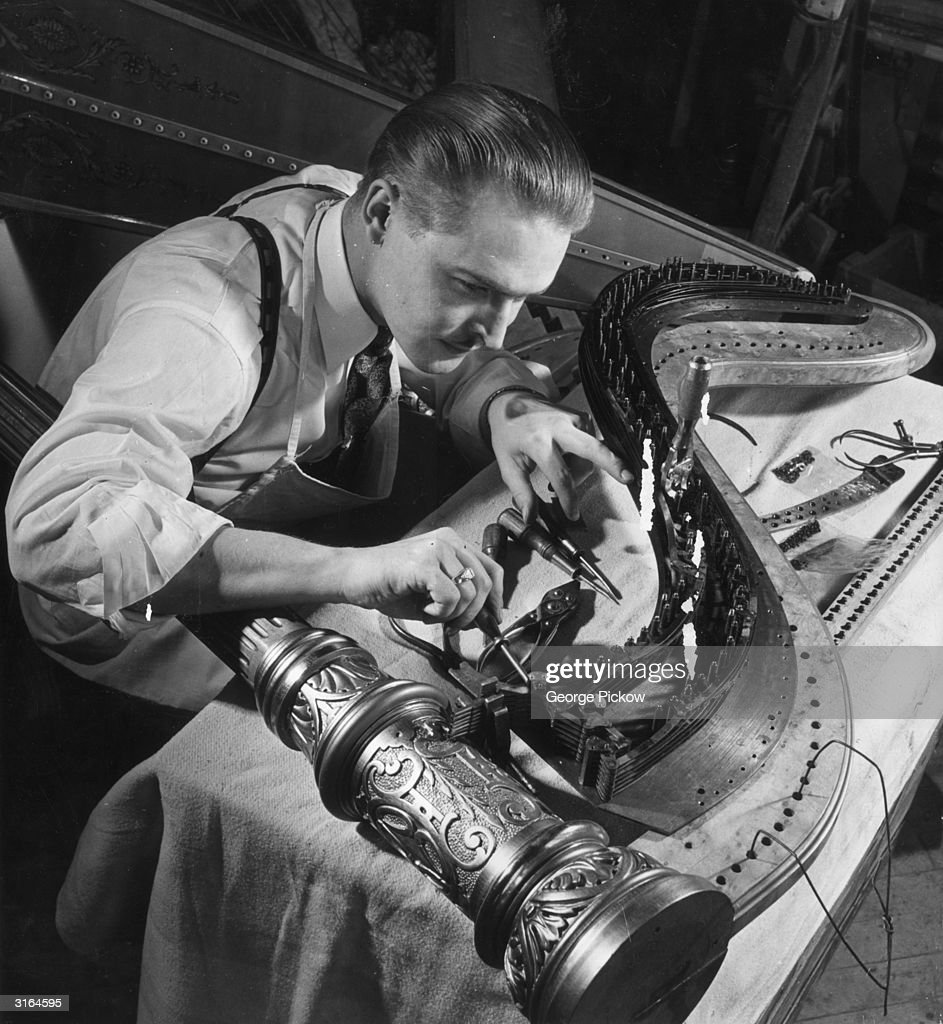 A master craftsman adjusts the foot pedals during completion of a concert harp. Having to work within the cramped confines of the harp's body makes his task all the more complicated.