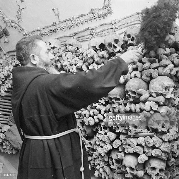 A monk dusts down the remains of his dead comrades in the tombs and the catacombs of a Capuchin monastery in Rome
