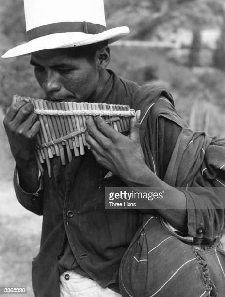 A musician from Azuay in Ecuador plays a set of rudimentary panpipes