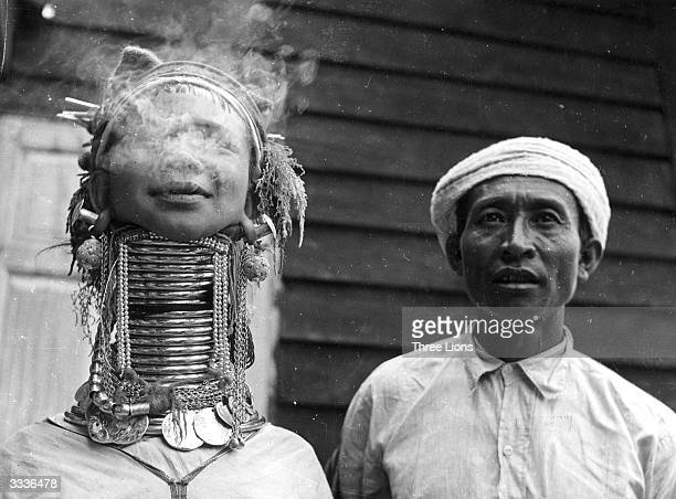 A Padaung or Kayan woman exhales smoke Originally a Mongolian tribe the Padaung have been assimilated into the Karen group native to Mayanmar A...