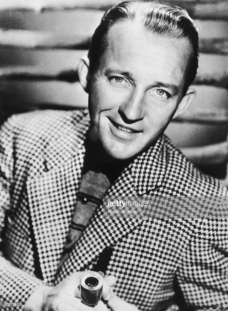 A portrait of actor and singer Bing Crosby wearing a houndstooth blazer holding a pipe