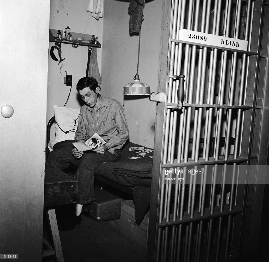A prisoner at the Iowa State Penitentiary in Fort Madison reading his Christmas cards in his cell.