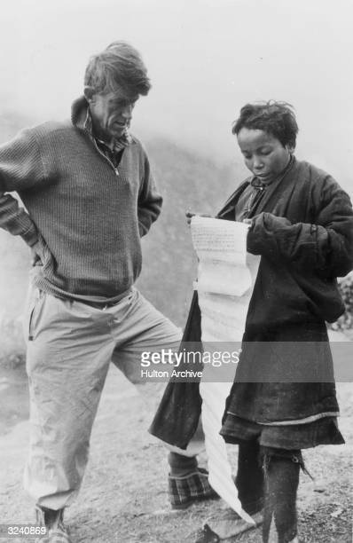 A sherpa boy presents Sir Edmund Hillary with a petition for a school which they both worked to build