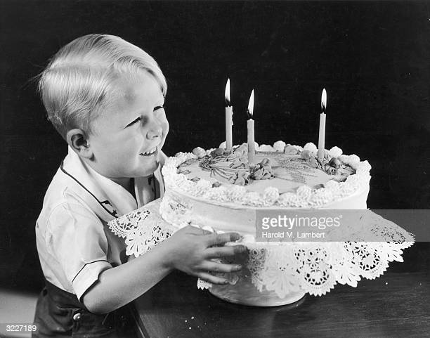 A small blonde boy smiles as he clutches a large birthday cake with three lit candles
