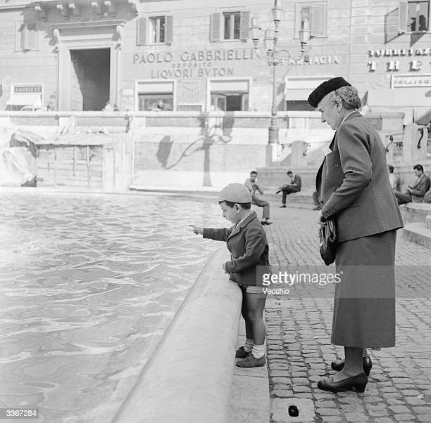 A small boy with his grandmother pointing out the coins thrown into the Trevi fountain in Rome