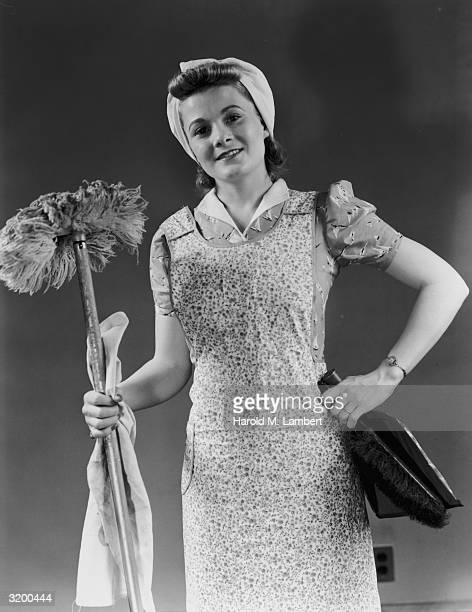 A smiling housewife holds a large dust mop a broom and dustpan