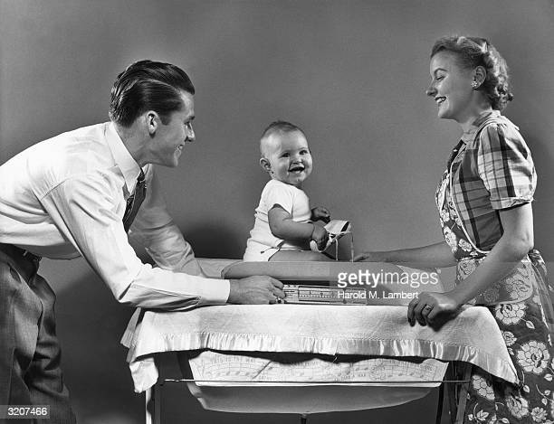 A smiling young couple weighs a laughing baby on scale atop changing table