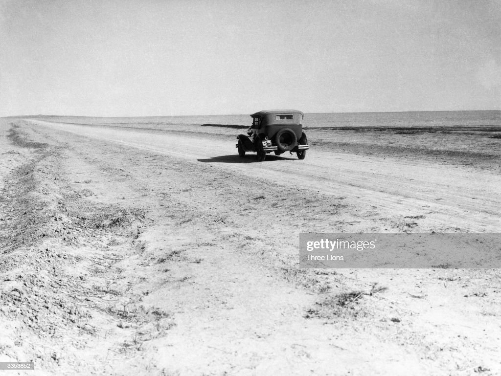 A solitary car driving along a desert road in the region of Ctesiphon, Iraq.