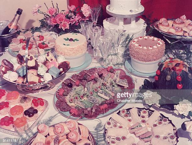 A table at a wedding reception laden with a garish variety of culinary delights such as cold meats salads volauvents and petitfours