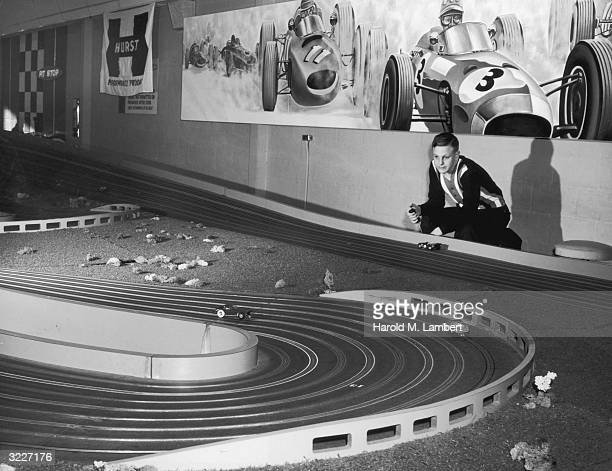 A teenage boy plays a large toy race car set in a rec room