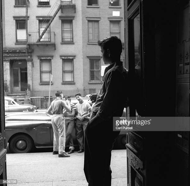 A teenage boy standing in the doorway of the New York tenement building where he lives