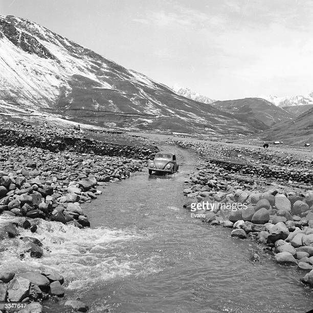 A Volkswagen Beetle fords a stream on the road from Cuzco to Ayacucho