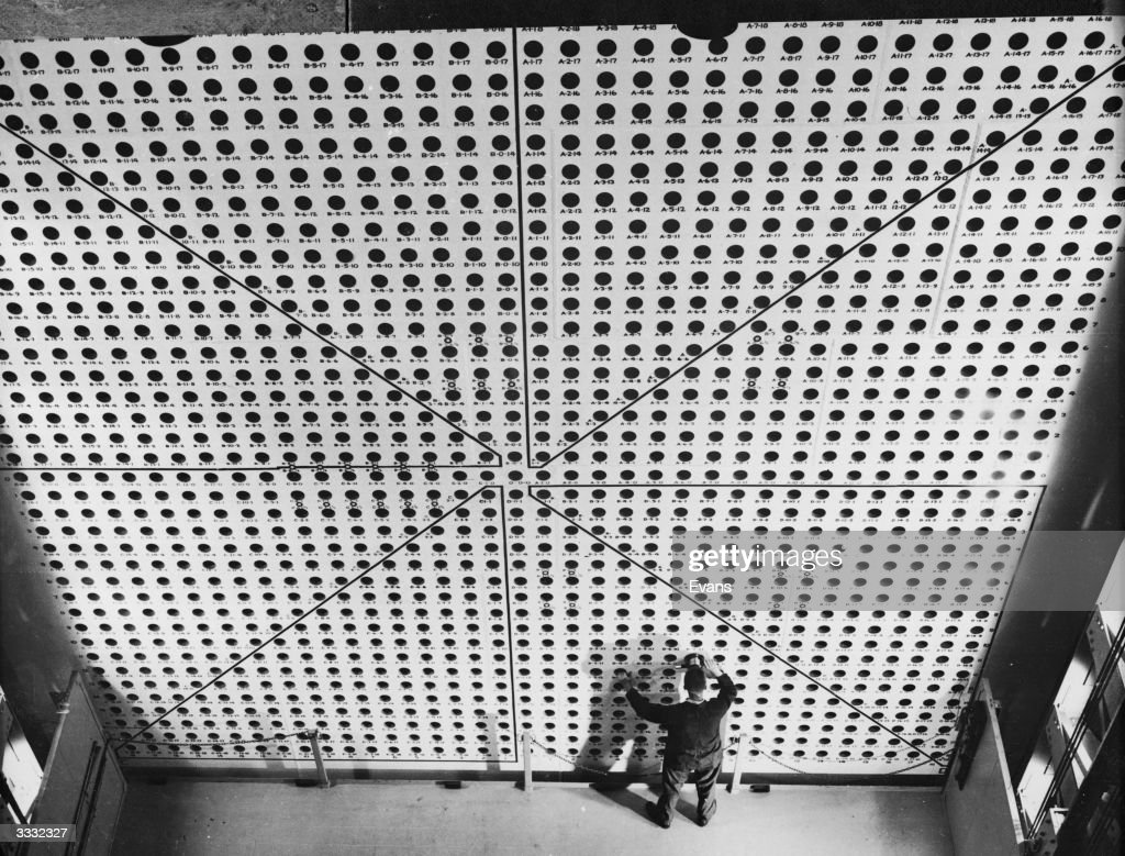 A wall of holes spaced eight inches apart where pure uranium is inserted into the atomic reactor at Brookhaven National Laboratories. The platform that the technician is standing on elevates to enable him to reach any level of the reactor face.