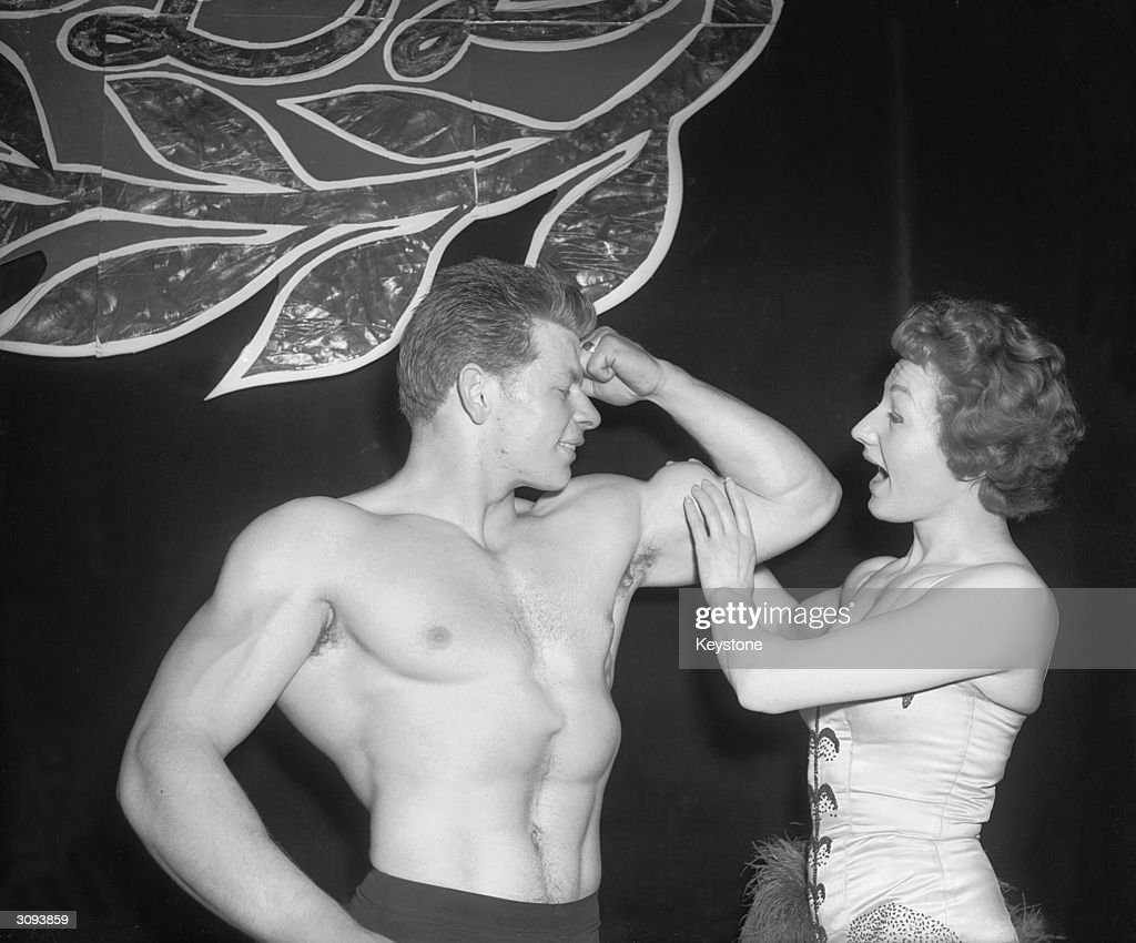 A woman admires the muscles of labourer Henry Sidney Downs, a contestant in the Mr Adonis and Mr Body Beautiful competitions held at the Scala Theatre.