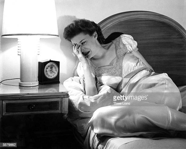 A woman crying as she looks at her bedside clock
