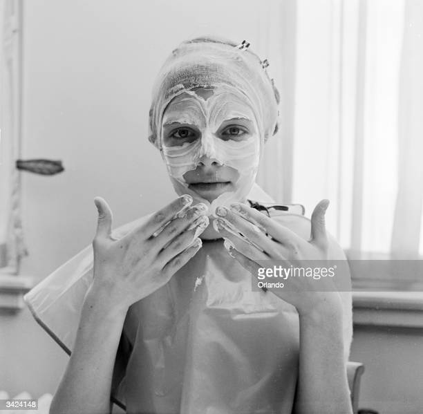 A woman gently applying skin cream to her face with the tips of her fingers