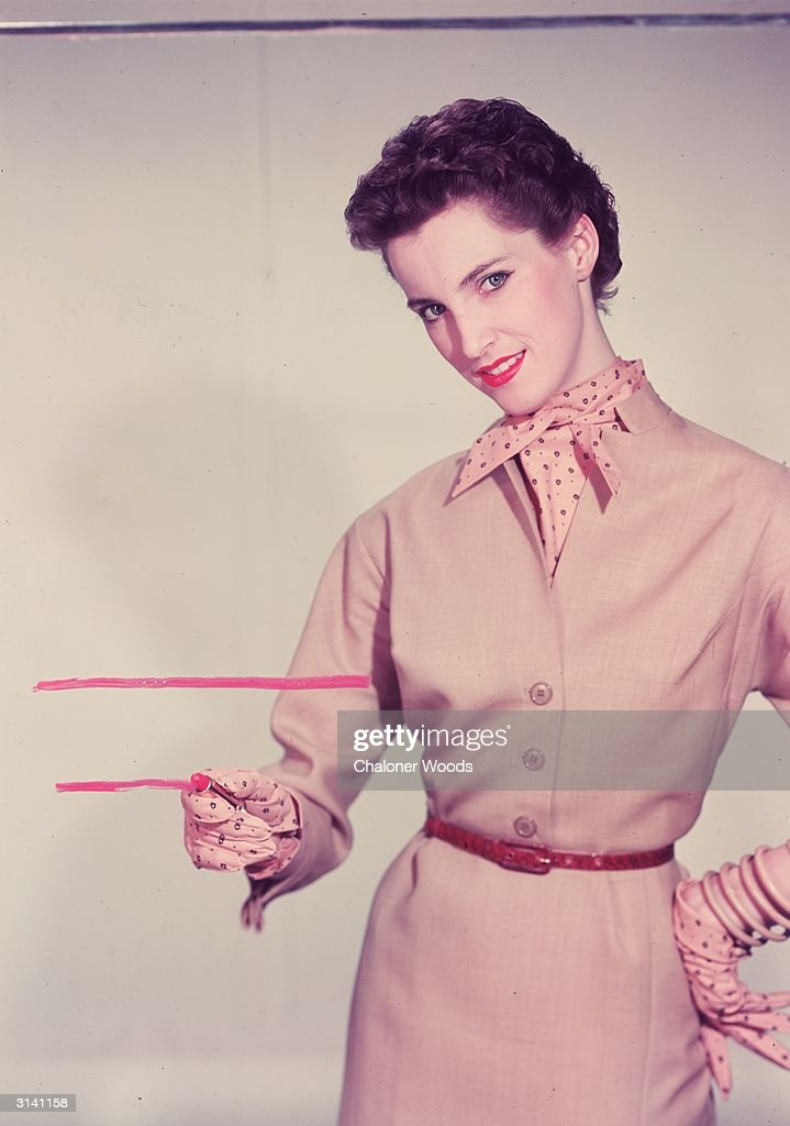 A woman in a belted cream dress with a spotted cravat and gloves draws a pink line on a pane of glass with her lipstick.
