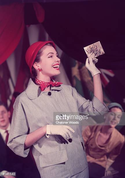 A woman in a black and white pinstripe suit with white gloves and a red hat and neckscarf looks laughingly at a small picture of a royal procession