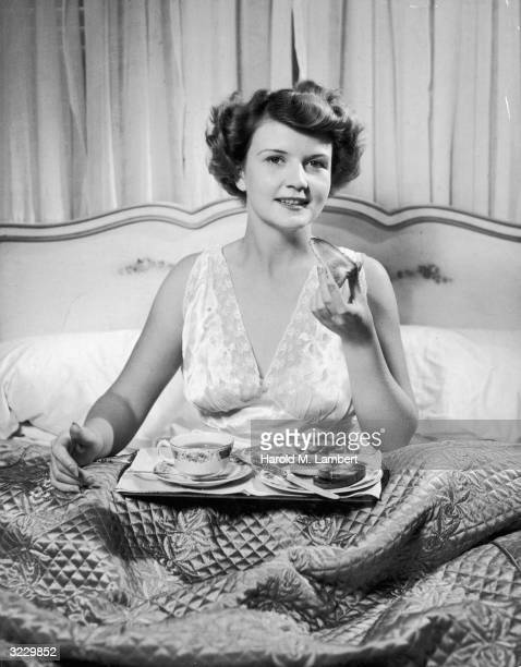 A woman in a nightgown sits under the covers having breakfast in bed She is eating from a breakfast tray bearing toast and coffee