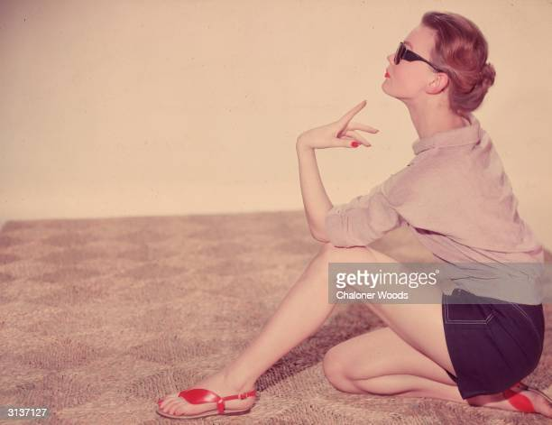 A woman in shorts and sandals sits down on a rafia mat to absorb the rays of the sun