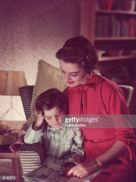 A woman reading with her young son at home He is already wearing his pyjamas and ready for bed