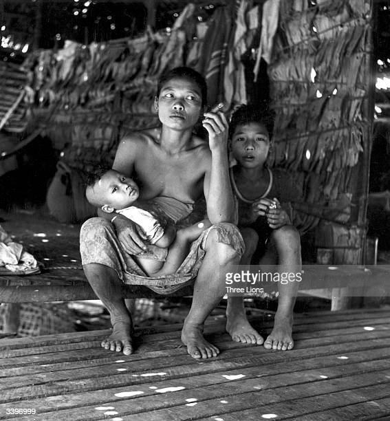 A woman smoking a cigar with her children in her home in Burma now Myanmar