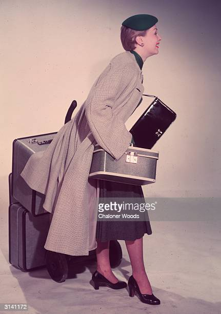 A woman starts off on a journey with a full set of luggage two suitcases a handbag and a beauty case