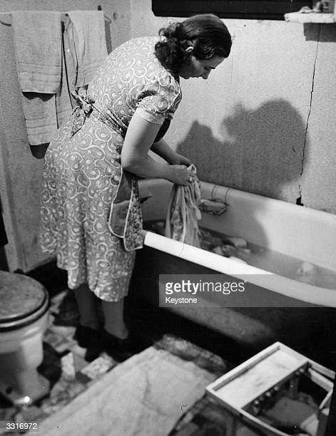 A woman washing laundry by hand in the bath
