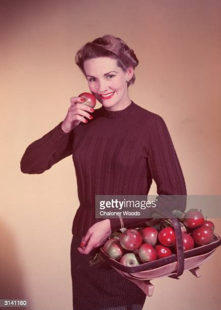 A woman wearing a dark brown jersey and carrying a basket of apples