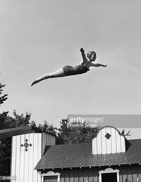 A woman wearing a swimsuit and bathing cap stretches her arms wide as she leaps high off a diving board and flies through the air