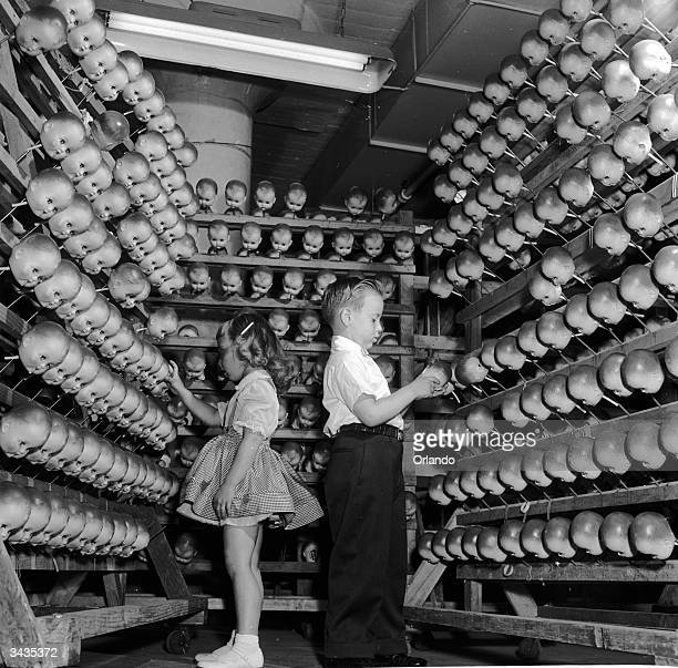 A young boy and girl inspecting dolls' heads at the Ideal Toy Company in Jamaica Long Island USA The company is one of the largest toy manufacturers...