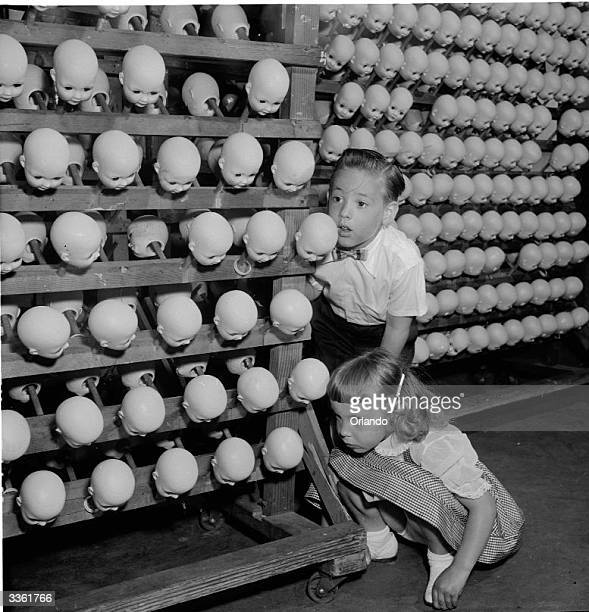 A young boy and girl looking at hundreds of dolls' heads at the Ideal Toy Company in Jamaica Long Island USA The company is one of the largest toy...