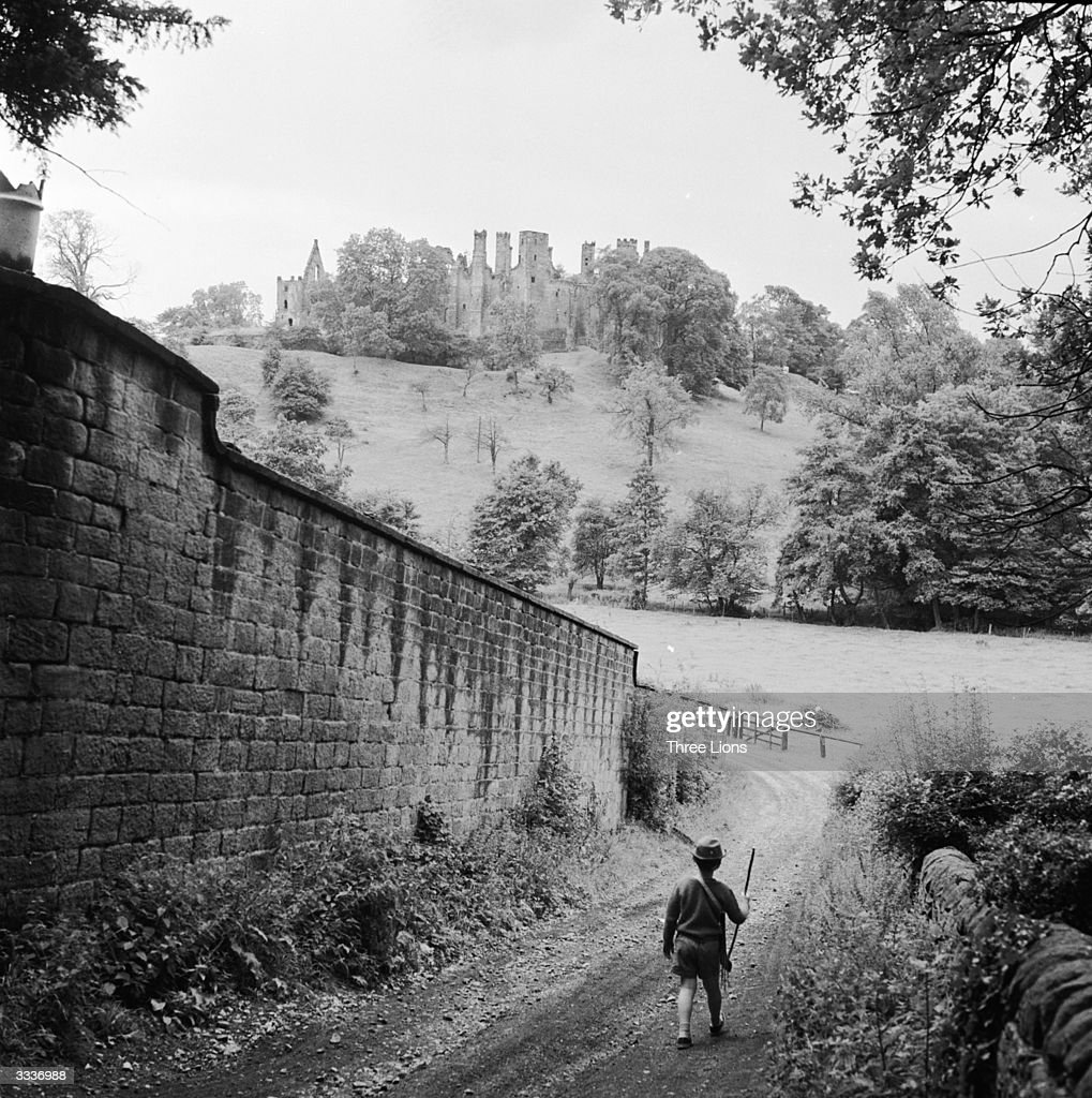 A young boy dressed as Robin Hood walking through Sherwood Forest with a bow and arrow On the hill in front of him are the ruins of Wingfield Manor...
